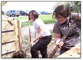 Girls turning compost